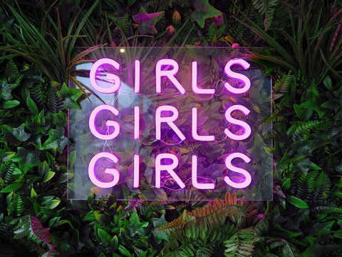 A pink neon sign saying 'Girls Girls Girls' against a garden backdrop.