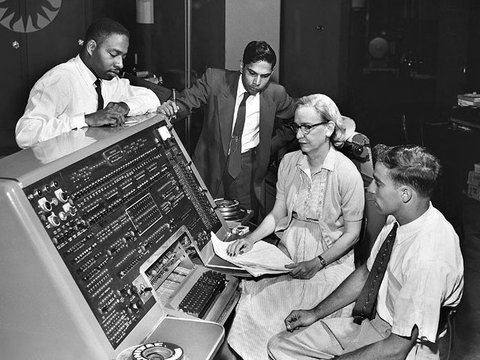 Grace Hopper sitting at the UNIVAC keyboard.